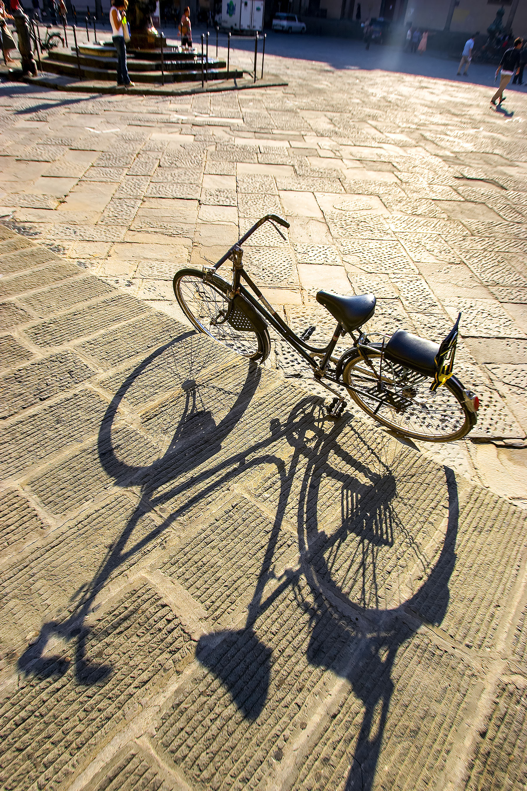 Bicycle in Plaza, piazza in Florence Italy with long shadow on cobblestone