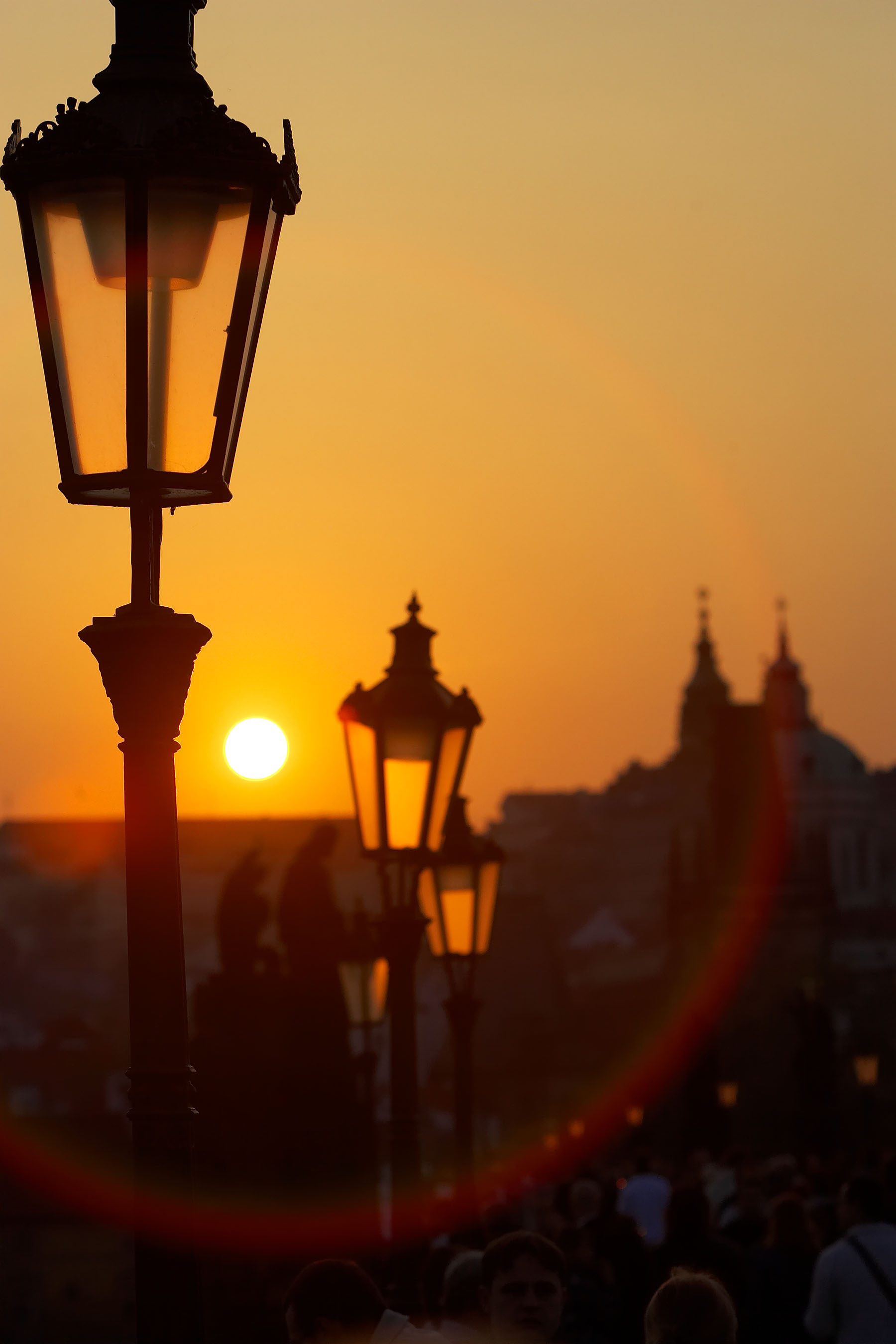 Lamp at dusk on the Charles Bridge over the Vlatva River in Prague, Czech Republic with Prague Castle in background